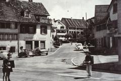 Bärenplatz, Bettswilerstr. Auch in Bäretswil hält das Auto um 1960 breiteren Einzug. Auf der Strasse nach Bettswil ist eine Mutter mit ihrem Töffli und dem Kind auf dem Gepäckträger zu erkennen.