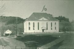 Ref. Kirche, kleiner Friedhof, Eingänge. Bis 1927 hat nur der Haupteingang Süd ein Vordach. Die Telefonstangen erinnern an erste Telefone, die es in Bäretswil seit 1887 gibt.