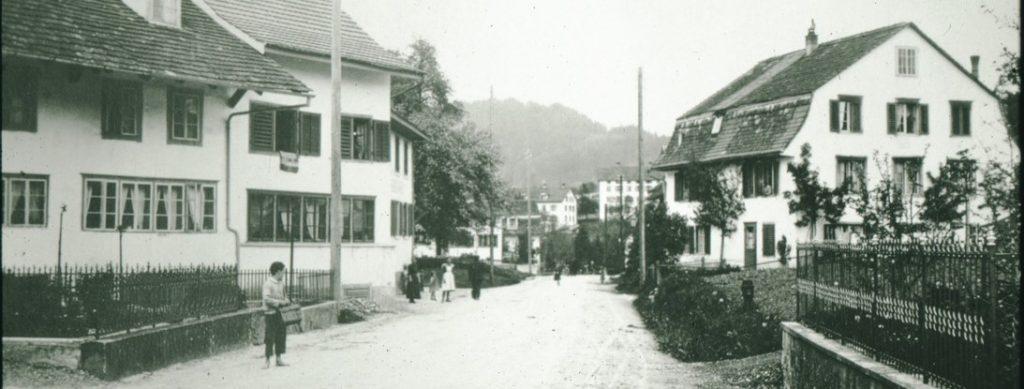 Wetzikerstrasse im Oberdorf Richtung Dorf, rechts Weberei, hinten Spörri Fabrik, ca. 1900